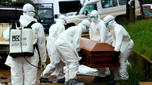 Burial team workers handling a casket with the human remains of an Ebola victim in Monrovia. Photo credit: Alexander Wiaplah