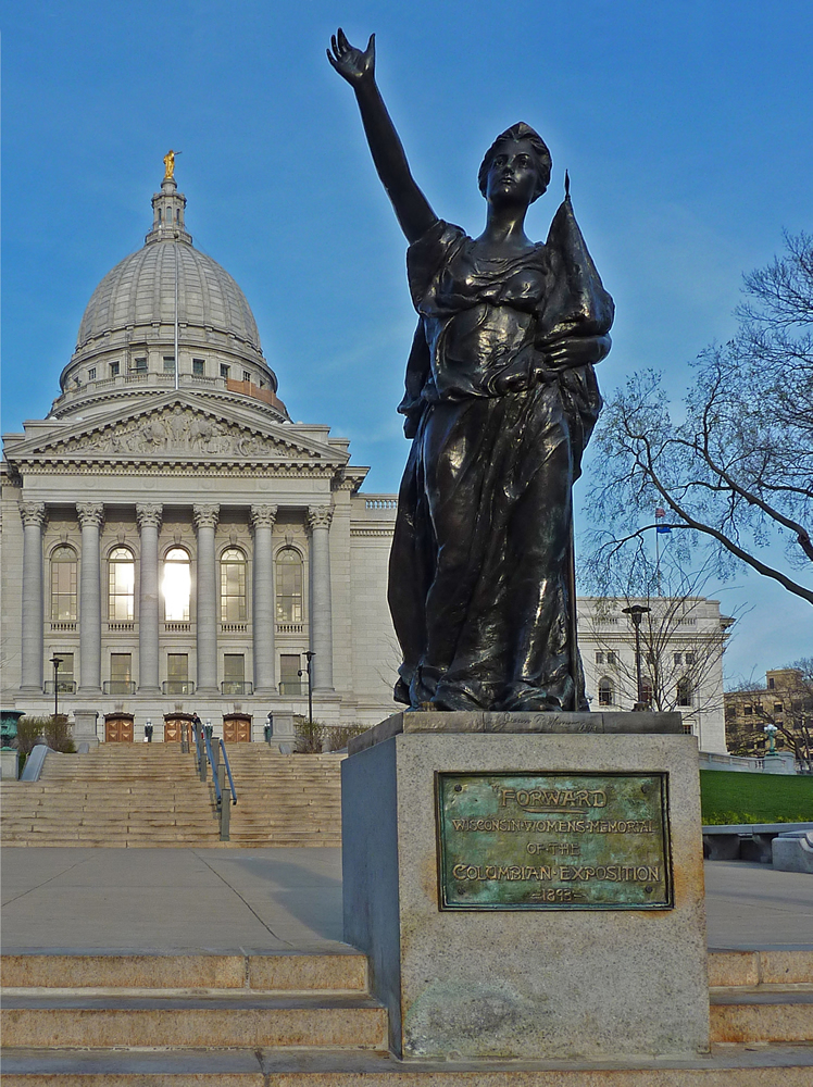 "The photo is of a copy of the figurehead statue ""Forward"", which was created at the Columbian World Exposition in Chicago (1893) by artist-in-residence Jean Pond Miner. The title of the statue adopts the motto of the State of Wisconsin, and funding was provided by the women of Wisconsin. Following display in Chicago, the statue was initially installed at the State Capitol in Madison, Wisconsin. It has now been removed to the interior of the Wisconsin Historical Society, and a copy is on display near the State Capitol at the corner of State Street and Mifflin Street."