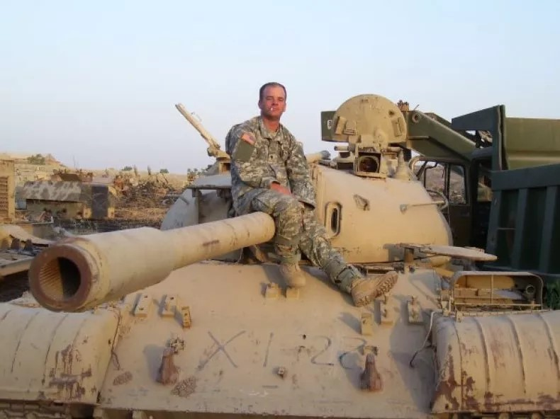 Chad Gibbs posing on top of a tank during a tour of duty in Iraq.